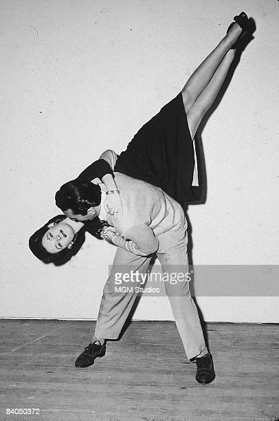 American actor Susan Peters hangs upside down while learning to jitterbug with dance champion Dean Collins for her role in the film 'Young Ideas' 1943