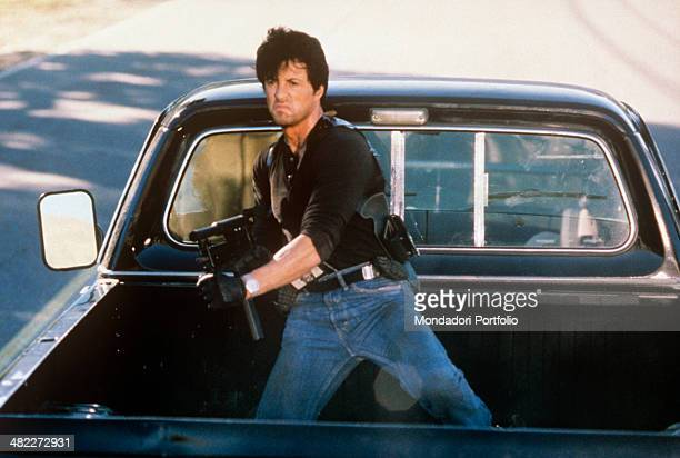 American actor Sylvester Stallone holding a light machine gun on a pick up in the film Cobra USA 1986
