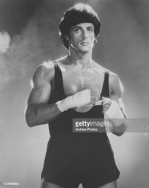 American actor Sylvester Stallone in a vest and shorts placing boxing tape on his hands circa 1970's