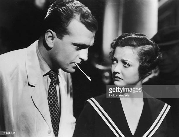 American actor Sylvia Sidney and British actor John Loder chewing a straw in a still from British director Alfred Hitchcock's film 'Sabotage'