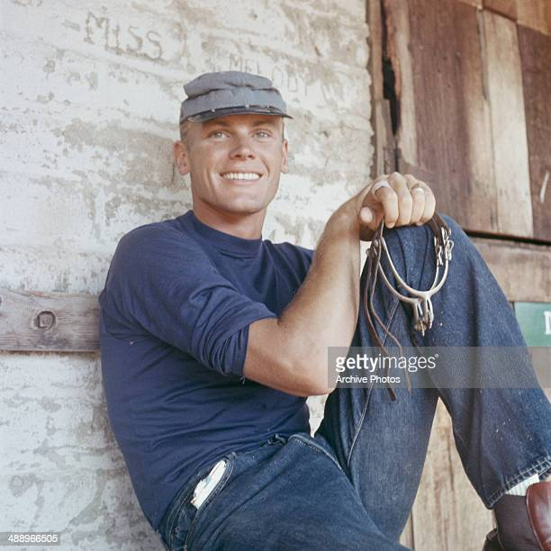 American actor Tab Hunter holding a pair of stirrups circa 1960