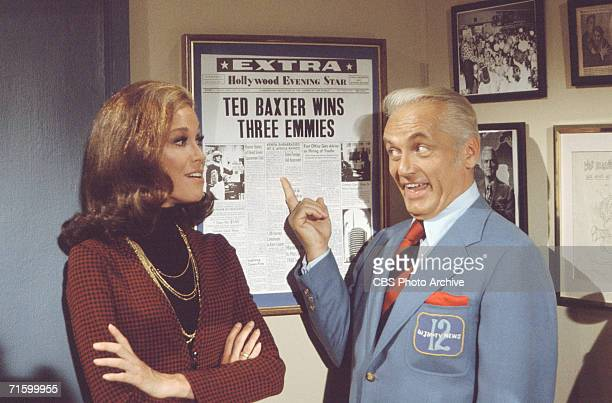 American actor Ted Knight , as Ted Baxter, looks at colleague Mary Tyler Moore, as Mary Richards, as he points to a newspaper headline which reads...