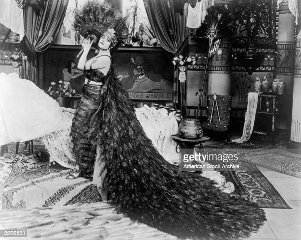 American actor Theda Bara holds a peacock feather fan next to a bed in a still from director J Gordon Edwards' film 'Cleopatra' Bara is wearing a...