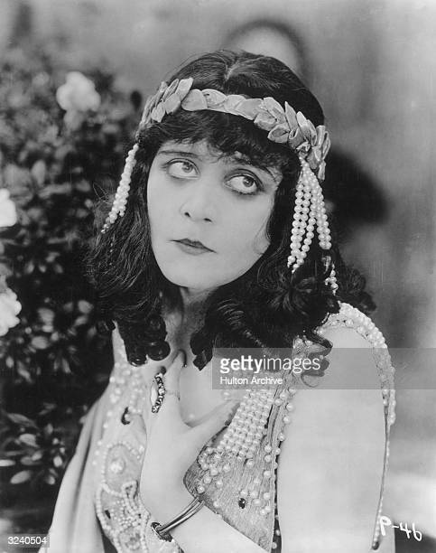American actor Theda Bara looks up holding one hand to her chest in a still from director J Gordon Edwards' silent film 'Salome' She wears a garland...