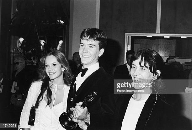 American actor Timothy Hutton holds his Best Supporting Actor Oscar statuette while posing with his girlfriend, actor Diane Lane, and his mother,...