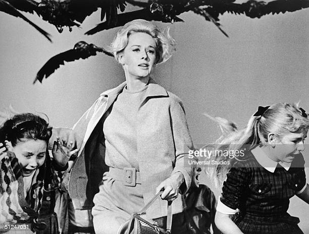 American actor Tippi Hedren and a group of children run away from the attacking crows in a still from the film 'The Birds' directed by Alfred...