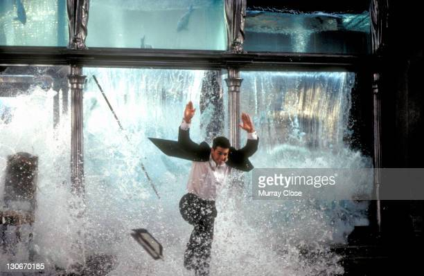 American actor Tom Cruise as Ethan Hunt escaping through the collapsing aquarium in a restaurant in a scene from the film 'Mission Impossible' 1996