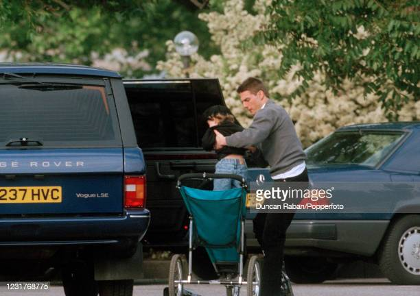 American actor Tom Cruise placing his son Connor into his buggy, whilst preparing to go rollerskating in Hyde Park in London, England on 8 June, 1995.
