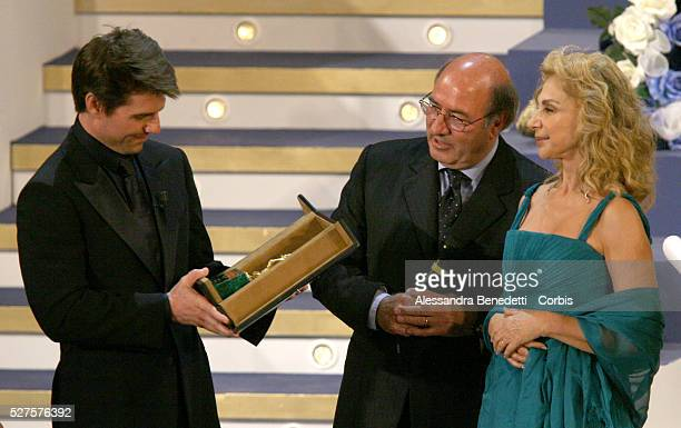 American actor Tom Cruise receives an honorary award from Italian art design Oscar winners Dante Ferretti and his wife Francesca Lo Schiavo during...