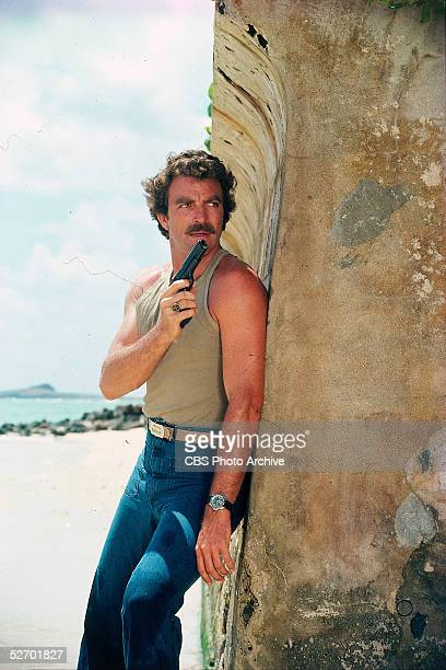 American actor Tom Selleck in character as private investigator Thomas Sullivan Magnum hides behind a seawall with an automatic pistol at the ready...