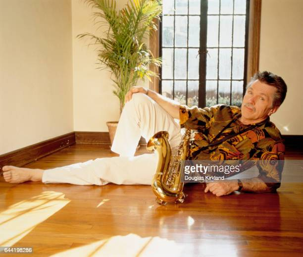 American actor Tom Skerritt relaxes with his saxophone in an empty room