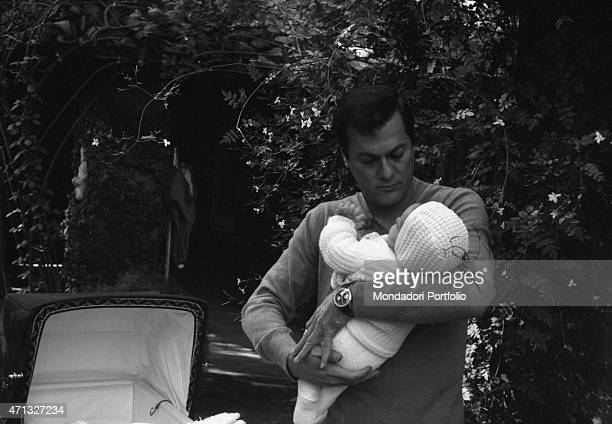 American actor Tony Curtis holding a baby Rome 1966