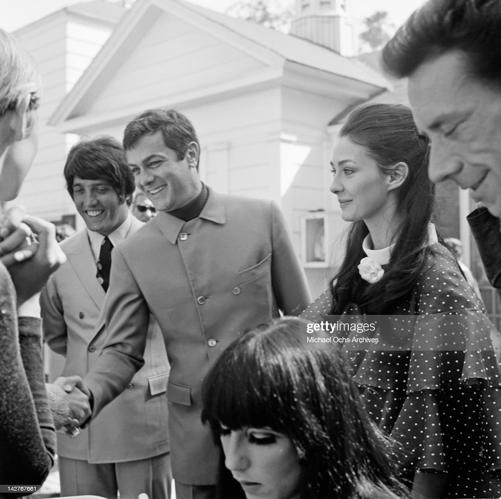 American actor Tony Curtis (1925 - 2010) with his wife, actress Christine Kaufmann, circa 1965. Twiggy's manager Justin de Villeneuve is on the left.