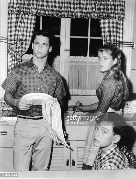 American actor Tony Dow washes dishes with a towel as he stands in the kitchen alongside an unidentified actress and Jerry Mathers who sits and gives...