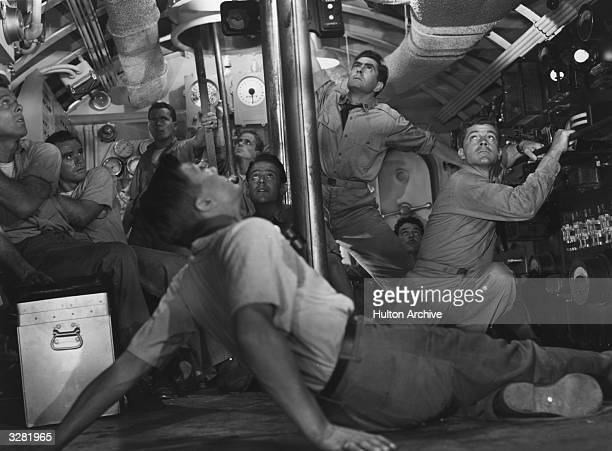 American actor Tyrone Power plays a submarine crew member in the film 'Crash Dive' a wartime romance directed by Archie Mayo for 20th Century Fox