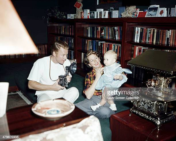 American actor Van Johnson photographing his wife stage actress Eve Abbott and their baby daughter Schuyler with a twinlens reflex camera circa 1949