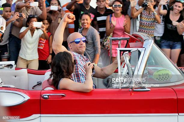 American actor Vin Diesel next to actress Michelle Rodriguez clenches his fist as he drives a US vintage car past Cuban fans at the end of a filming...