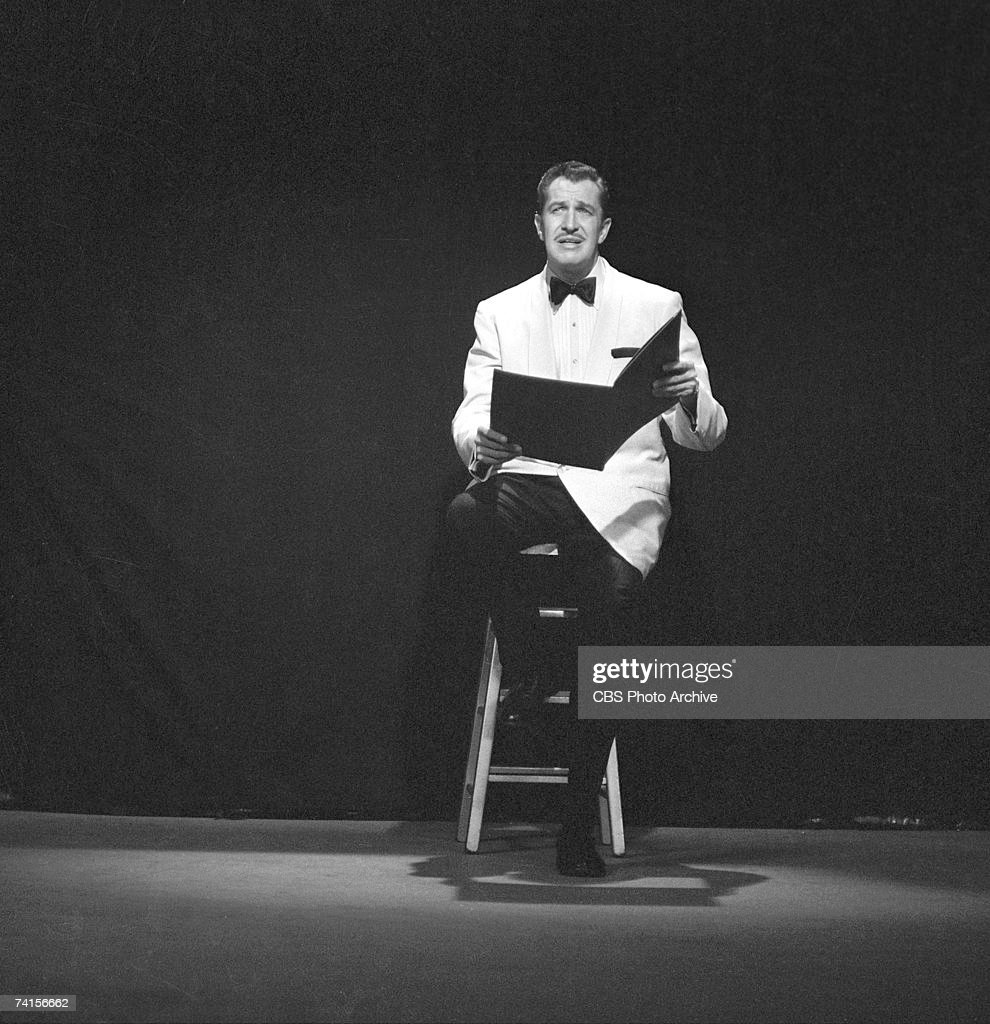 American actor Vincent Price (1911 - 1993) sits on a stool and reads from an oversized book during a skit on 'The Red Skelton Show,' May 13, 1958.