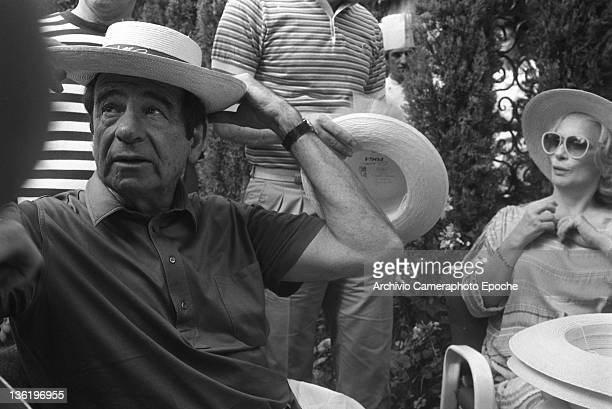 American actor Walter Matthau trying on a hat during a lunch at the at the Tribute To Ingrid Gala Lido Venice 1983