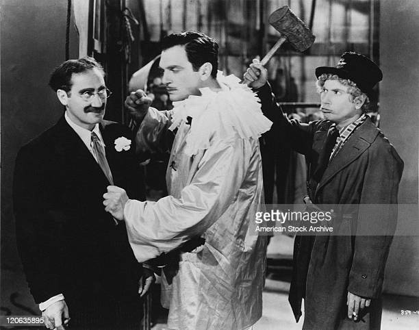 American actor Walter Woolf King threatens Groucho Marx unaware of Harpo Marx who is behind him with a mallet raised in a scene from 'A Night At The...