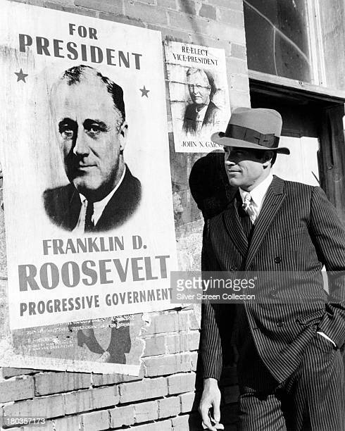 American actor Warren Beatty as Clyde Barrow posing next to a Roosevelt campaign poster in a promotional portrait for 'Bonnie And Clyde' directed by...