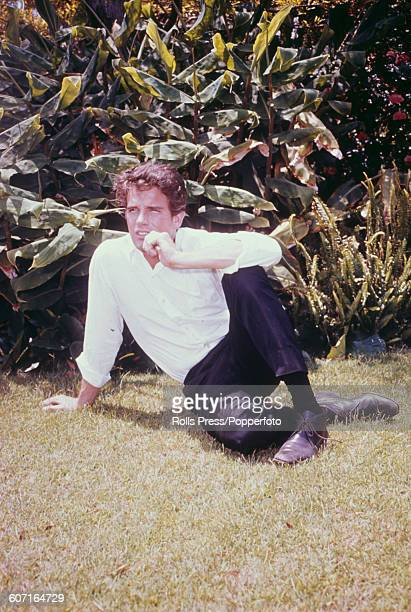 American actor Warren Beatty who plays the role of Clyde Barrow in the film Bonnie and Clyde pictured sitting on the grass in a garden in 1968