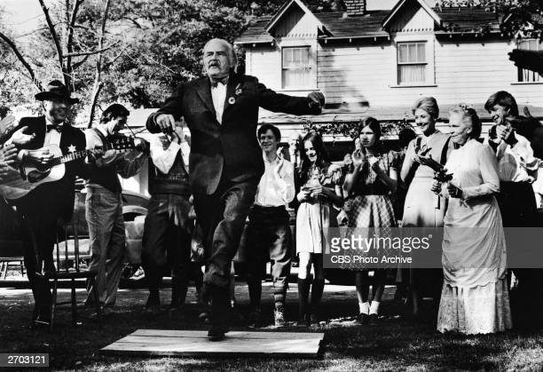 American actor Will Geer as Grandpa Walton dances a jig in front of the Walton house as the Walton family look on and clap in a scene from the...
