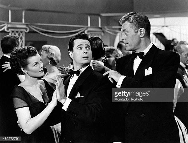 American actor Willard Parker touching American actor Larry Parks' shoulder while he's dancing with American actress Barbara Hale in the film...