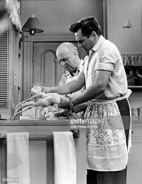 American actor William Frawley and Cuban-born American and musician actor Desi Arnaz wear aprons as they wash a couple of chickens that they scraped...