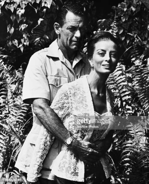 American actor William Holden stands embracing French fashion model and actress Capucine from behind in a scene from 'The 7th Dawn,' in which Holden...