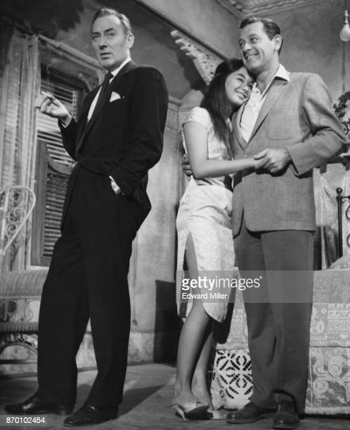 American actor William Holden with his arm around actress France Nuyen on the set of the film 'The World of Suzie Wong' at the MGM studios in Elstree...