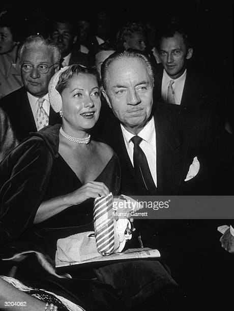 American actor William Powell and his third wife actor Diana Lewis share a bag of popcorn while sitting in the audience at an Ice Follies performance...