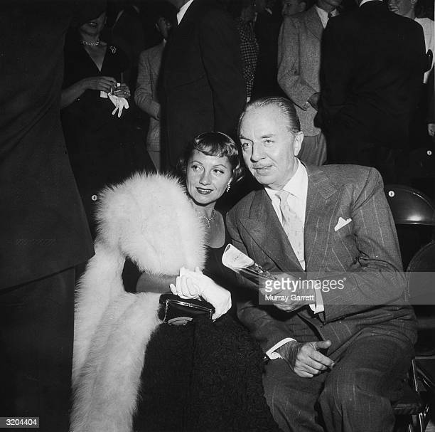 American actor William Powell sits on folding chairs with his wife American actor Diana 'Mousie' Lewis during an Ice Follies party Los Angeles...