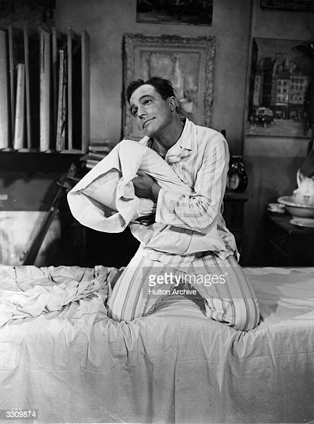 American actordancer Gene Kelly embraces his pillow in a scene from the musical romance 'An American in Paris' directed by Vincente Minnelli for MGM