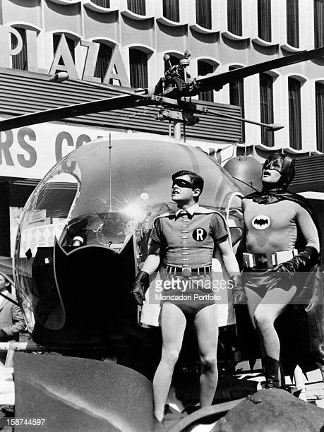 American actors Adam West and Burt Ward wearing the costumes of the comics superheroes Batman and Robin and looking up beside the Batcopter. They're...