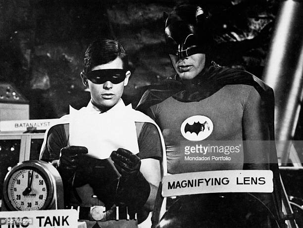 American actors Adam West and Burt Ward wearing the costumes of the comics superheroes Batman and Robin and reading a paper in the TV serie Batman....
