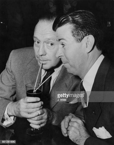 American actors and comedians Jack Benny and Dennis Day share a drink at the Prince of Wales Theatre in London as they prepare for a show at the...