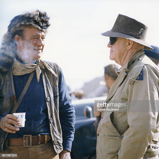 American actors and director John Wayne while directing his movie The Alamo near Brackettville Texas visits with veteran director and Wayne mentor...