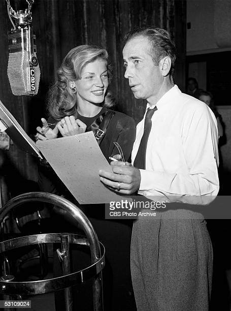 American actors and married couple Humphrey Bogart and Lauren Bacall read from scripts and speak into a hanging microphone as they perform on the...