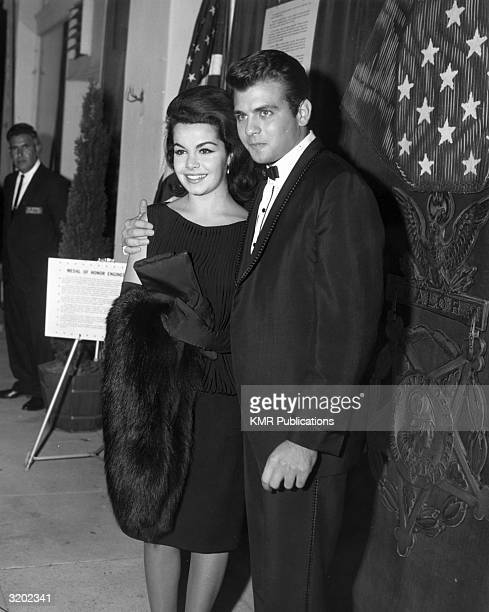 American actors and singers Annette Funicello and Fabian smile while standing with arms around each other in front of a largescale replica of a Medal...