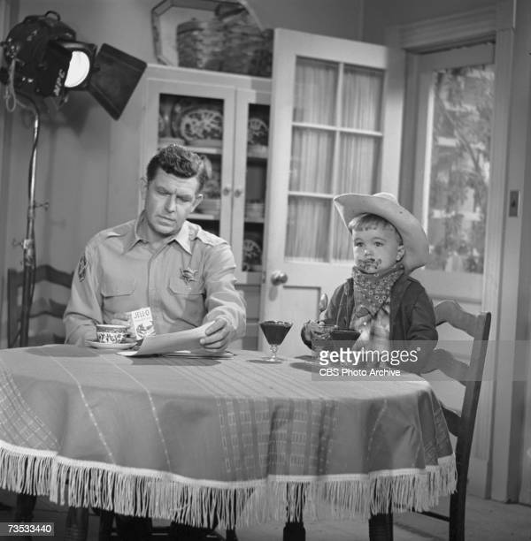 American actors Andy Griffith and 3yearold Clint Howard sit at a table on the set of 'The Andy Griffith Show' during the filming of a commercial for...