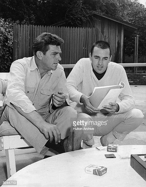 American actors Andy Griffith and Jim Nabors discuss a script for Nabors's television show 'Gomer Pyle USMC' in the garden of Griffith's home