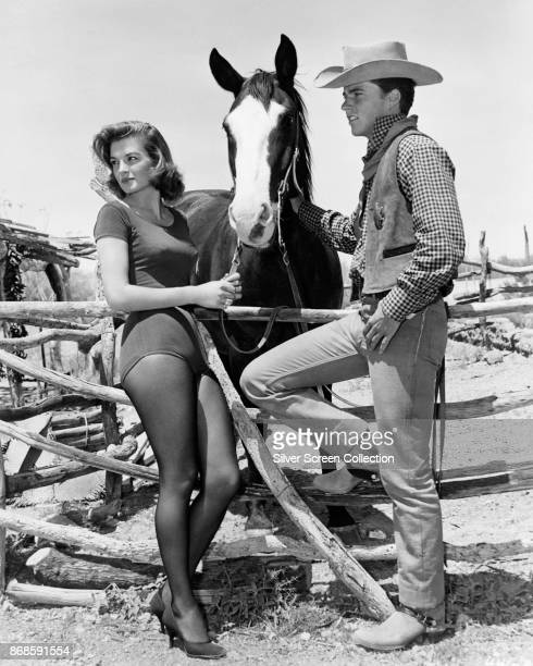 American actors Angie Dickinson and Ricky Nelson hold a horse in a scene from the film 'Rio Bravo' 1959