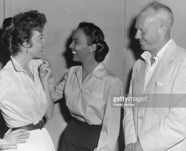 American actors Ava Gardner and Dorothy Dandridge talk while Australianborn director John Farrow looks on Farrow was directing Gardner in 'Ride...