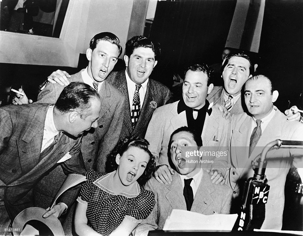 American actors Bert Lahr (1895 - 1967) (far right), Ray Bolger (1904 - 1987) (back row, right), Judy Garland (1922 - 1969) (sitting, right), composer Harold Arlen (1905 - 1986) (sitting left), and various MGM and music publishing executives sing songs from the 1939 film musical 'The Wizard of Oz' around a microphone in the NBC radio studio, circa 1939.