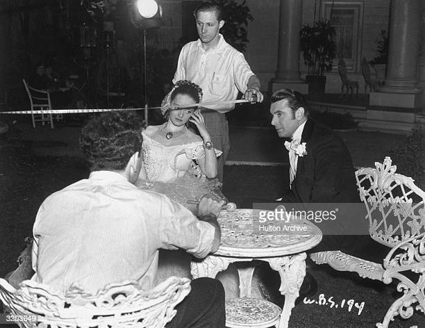 American actors Bette Davis and George Brent sit on lawn furniture while a crew member uses a measuring tape between takes on the set of director...