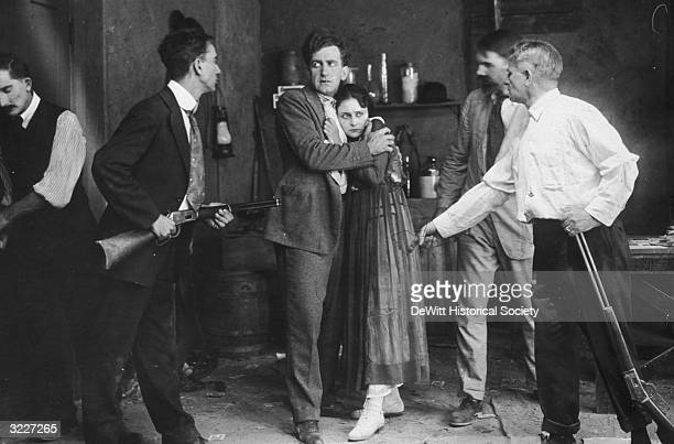 American actors Betty Howe and George Connor embracing as they are held up at gunpoint by a group of men in a still from the silent film 'Beatrice...