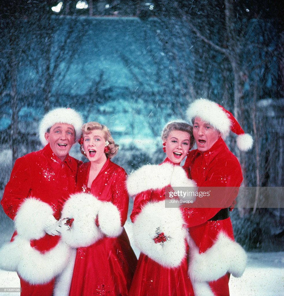 American actors Bing Crosby (1903 - 1977), Rosemary Clooney (1928 - 2002), Vera-Ellen (1921 - 1981), and Danny Kaye (1913 - 1987) sing together, while dressed in fur-trimmed red outfits and standing in front of a stage backrop, in a scene from the film 'White Christmas,' directed by Michael Curtiz, 1954.