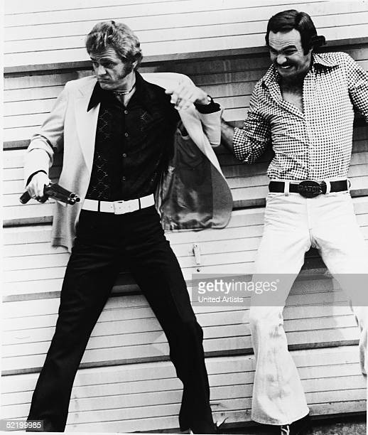 American actors Burt Reynolds and Jerry Reed duck against a garage wall in order to avoid gunfire in a still from the film 'Gator,' directed by...
