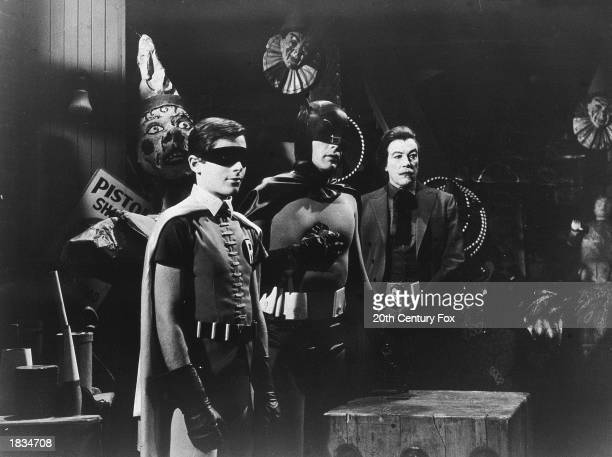 American actors Burt Ward, as Robin, Adam West, as Batman, and Cesar Romero , as The Joker, stand in a room with circus props in a still from the...